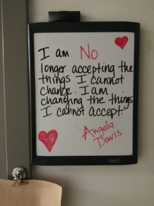 """Image of a white board that reads """"I am no longer accepting the things I cannot change. I am changing the things I cannot accept. Angela Davis"""""""